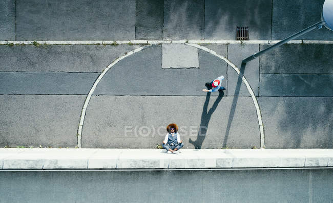 View from above young man meditating on urban sidewalk — Stock Photo