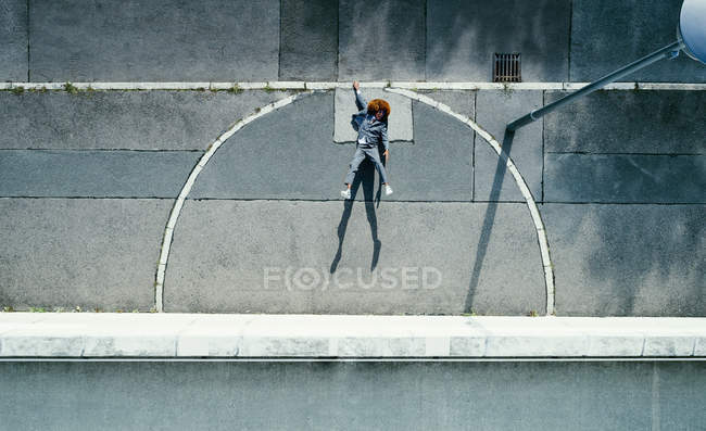 View from above young man with afro hanging from urban curb — Stock Photo