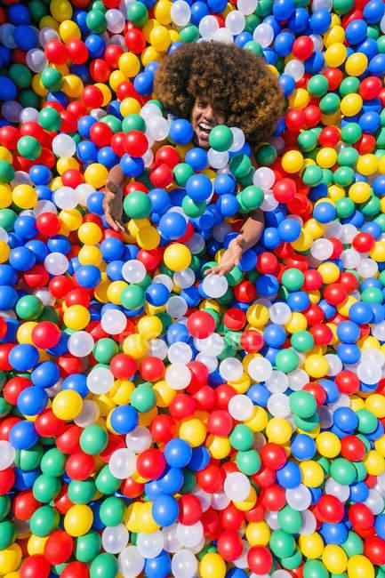 Retrato joven juguetón en piscina de bolas multicolor - foto de stock