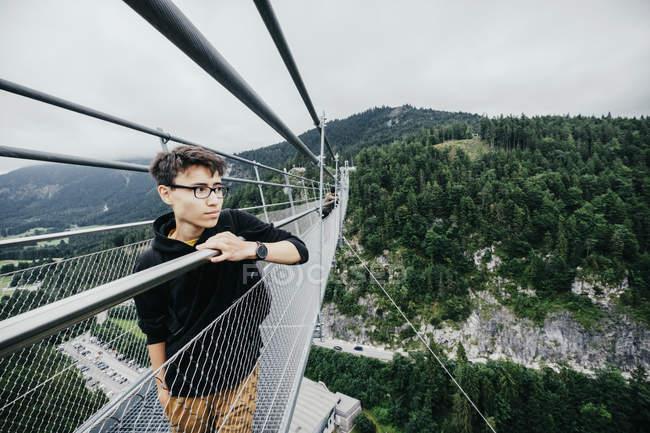 Ragazzo adolescente in piedi sulla Highline 179 ponte sospeso, Tirolo, Austria — Foto stock