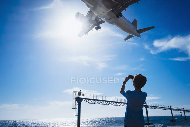 Boy with camera phone photographing airplane flying low overhead near Lanzarote Airport — Stock Photo