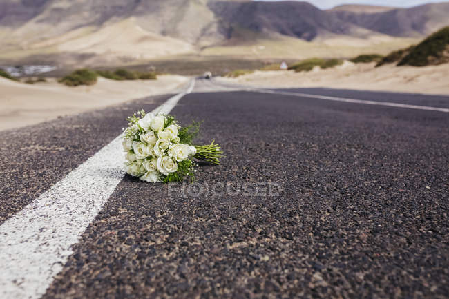 Bridal bouquet with roses laying on remote road — Stock Photo