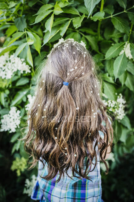 Girl with flowers in hair at blooming bush — Stock Photo