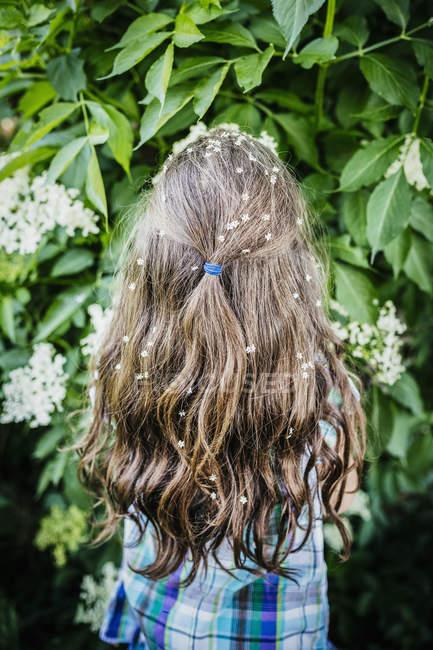 Девушка с цветами в волосах на цветущих кустах — стоковое фото