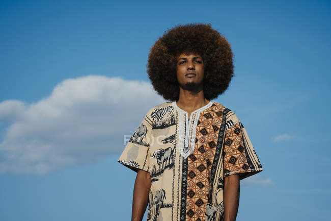 Portrait confident young man with afro standing against blue sky with clouds — Stock Photo