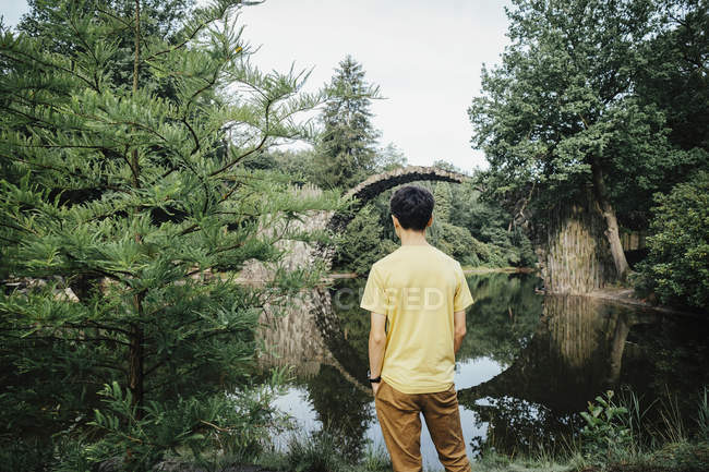 Teenage boy looking at tranquil Rakotzbruecke Devils Bridge, Rakotzbruecke, Brandenburg, Germany — Stock Photo