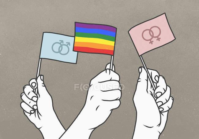 Противостоящие руки размахивают радугой и гендерными флагами — стоковое фото
