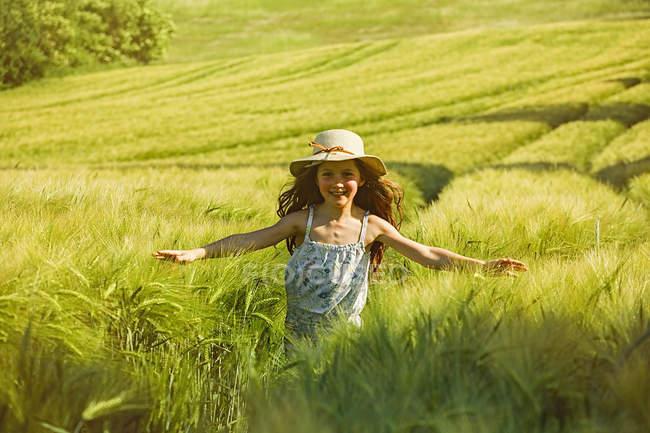 Porträt glückliches, unbeschwertes Mädchen läuft sonniges ländliches Feld — Stockfoto