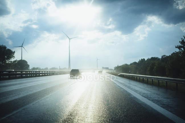 Солнце на мокром асфальте с ветреными турбинами на расстоянии, Берлин, Германия — стоковое фото