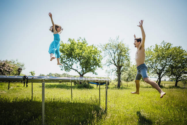 Playful father and daughter jumping on trampoline in sunny summer back yard - foto de stock