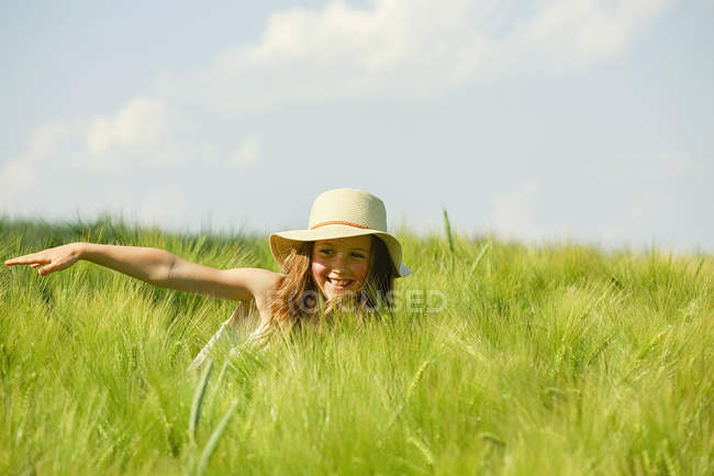 Carefree, happy girl in sunny rural green wheat field — Stock Photo