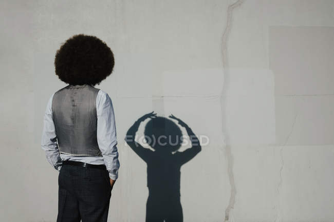 Young man with afro watching gesturing shadow on sunny wall — Stock Photo