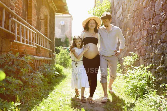 Familia embarazada caminando por soleada granja - foto de stock