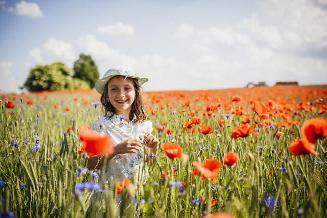 Retrato feliz, chica despreocupada en el campo de amapola roja rural soleado, idílico - foto de stock
