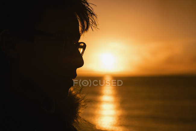 Profilo silhouette adolescente ragazzo guardando il tramonto sull'oceano — Foto stock