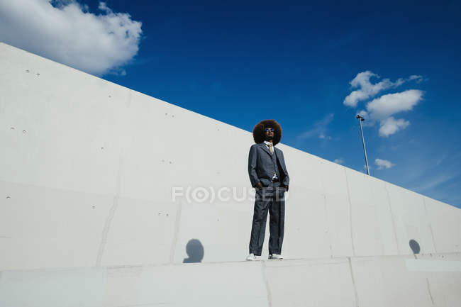 Portrait confident, cool, well-dressed young man with afro standing on urban wall — Stock Photo