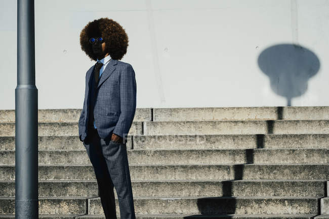 Portrait cool, well dressed young man with afro at urban steps — Stock Photo