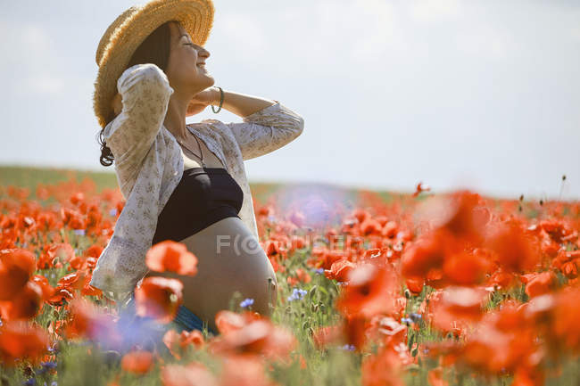 Carefree pregnant woman in sunny, idyllic rural red poppy field — Stock Photo