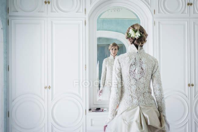 Elegant bride in lace wedding dress at mirror — Stock Photo