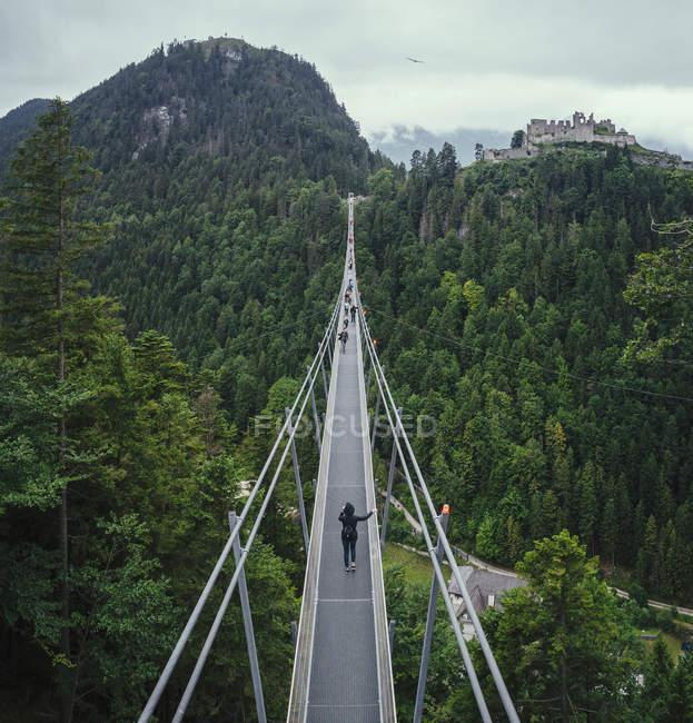 Personnes traversant le pont suspendu au-dessus de la cime des arbres verts, Tyrol, Autriche — Photo de stock