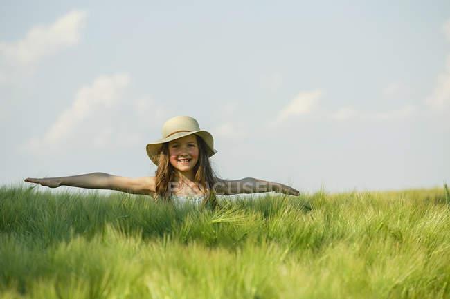 Портрет беззаботной девушки с вытянутыми руками на солнечном, сельском зеленом поле — стоковое фото