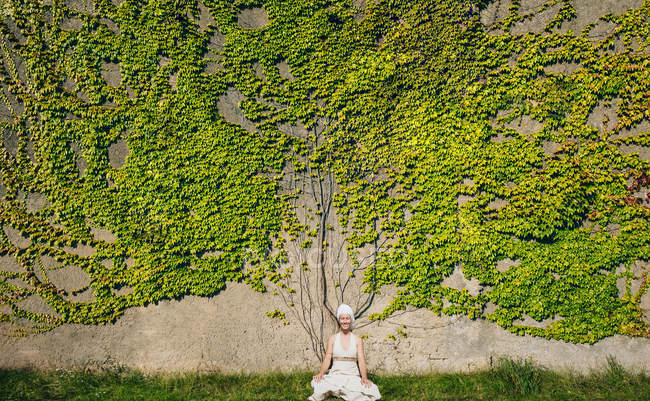 Portrait of woman meditating at wall overgrown with ivy — Stock Photo