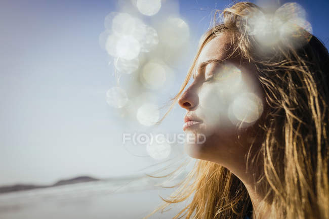 Serene woman basking in sunshine on beach — Stock Photo