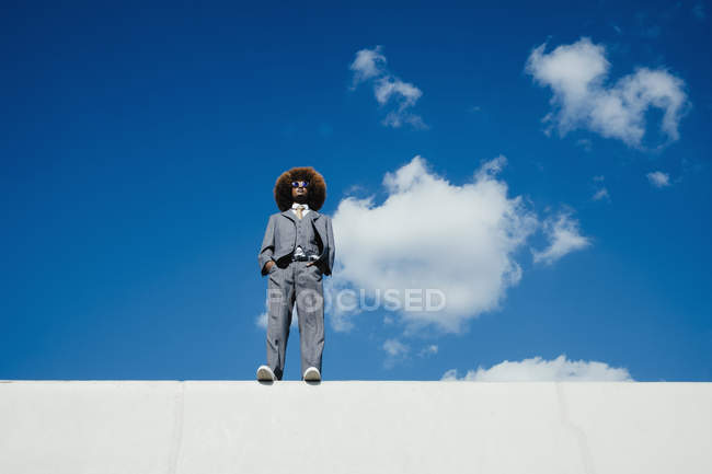 Confident, cool, well-dressed young man with afro standing on sunny wall against blue sky — Stock Photo
