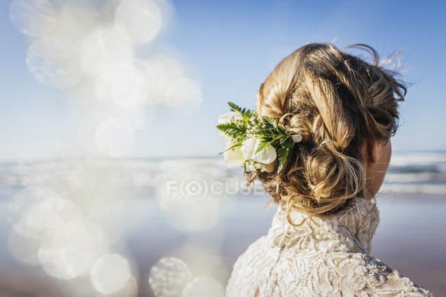 Novia rubia con flores en el pelo en la playa soleada - foto de stock