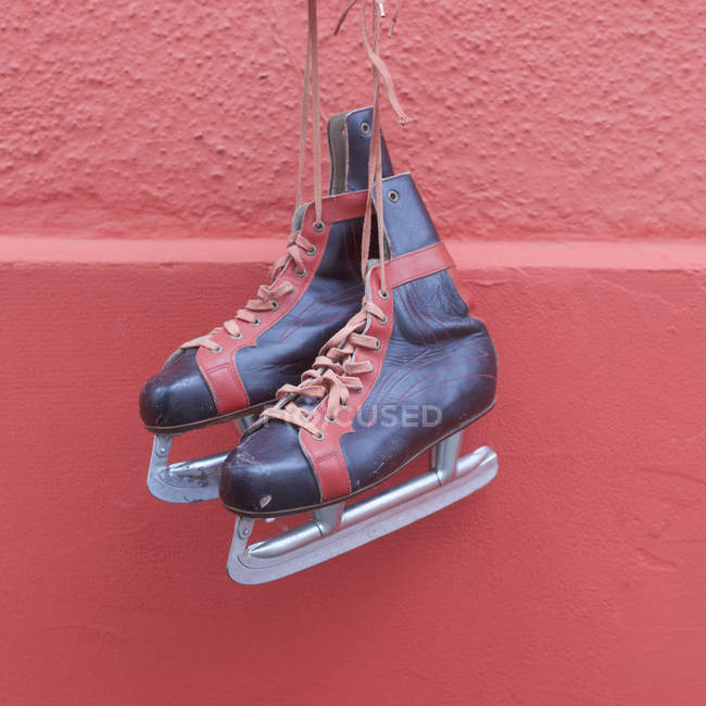 Ice skates hanging against red wall — Stock Photo