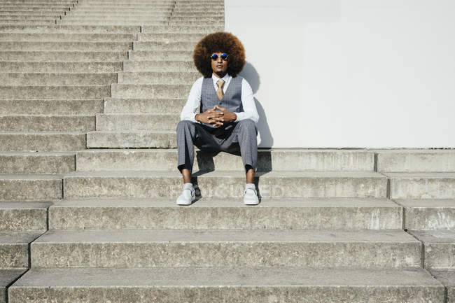 Portrait confident, cool, well-dressed young man with afro sitting on urban steps — Stock Photo