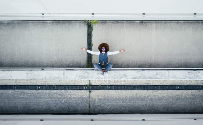 View from above portrait exuberant young man on urban ledge — Stock Photo