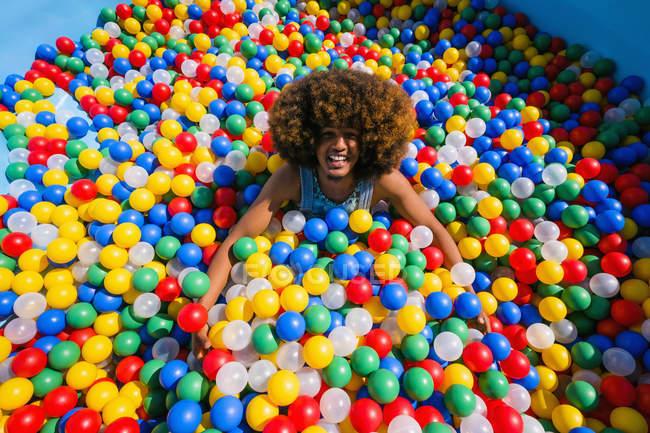 Ritratto esuberante giovane che gioca in piscina a sfera multicolore — Foto stock