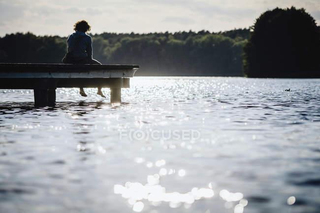Mujer relajándose en el borde del muelle del lago soleado - foto de stock