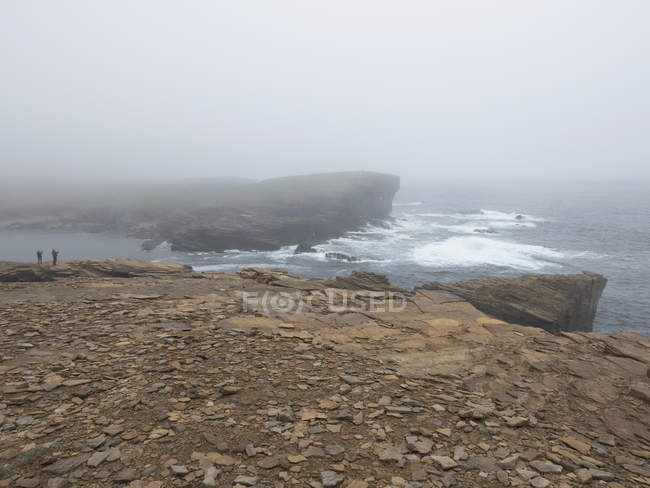 Tourists on rugged cliff enjoying scenic ocean view, Orkney Islands, Scotland — Stock Photo