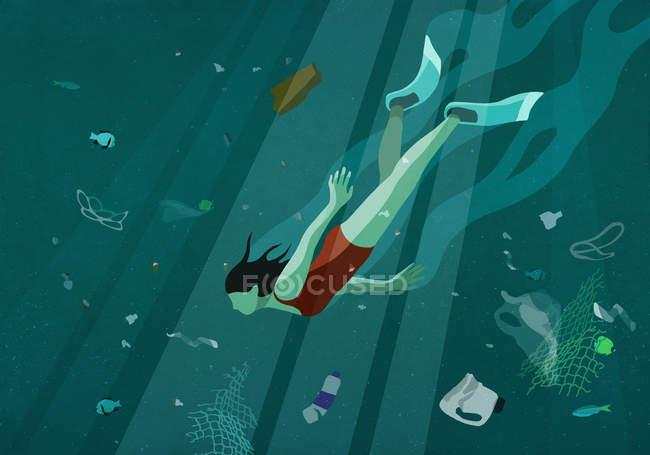 Женщина плавает под водой в море среди загрязнения — стоковое фото