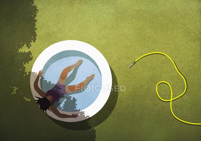 Беззаботная женщина отдыхавая в заднем дворе надувной бассейн — стоковое фото