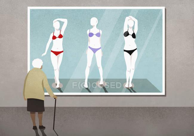 Mulher sênior olhando para biquínis em manequins fotografia na galeria de arte — Fotografia de Stock