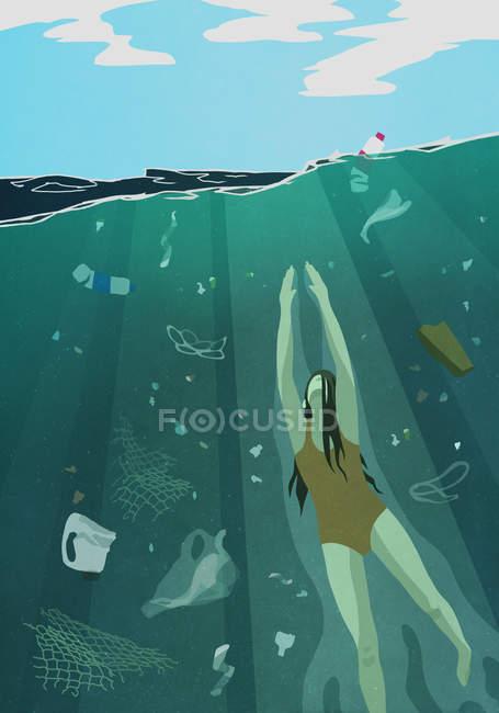 Женщина плавает под водой в океане в окружении загрязнения — стоковое фото
