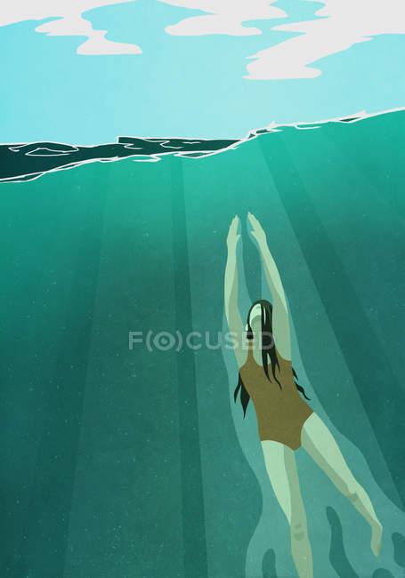 Плавающая женщина, поднимающаяся на поверхность океана — стоковое фото