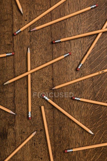 Vista desde arriba de los lápices sobre la superficie de madera - foto de stock