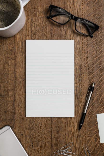 Vista do bloco de notas alinhado em branco acima na mesa de madeira — Fotografia de Stock