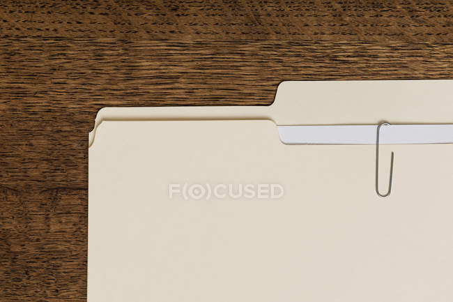 View from above manila folder and paperclip on wooden surface — Stockfoto