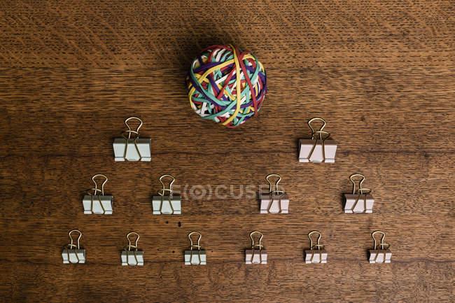 Vista de acima clipes de aglutinante e bola elástica na mesa de madeira - knolling — Fotografia de Stock