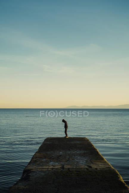 Хлопчик в Толстовка стояв на океанському пристані, Вікторія, Британська Колумбія, Канада — стокове фото