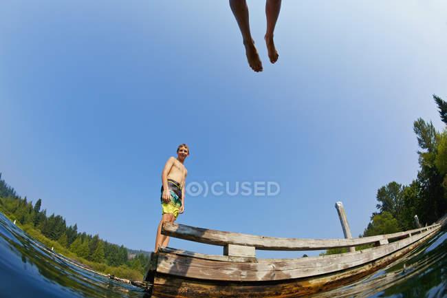Garçons sautant du dock dans le lac ensoleillé d'été — Photo de stock