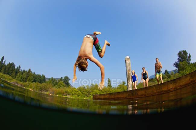 Garçon faisant un saut périlleux outre du dock dans le lac ensoleillé d'été — Photo de stock