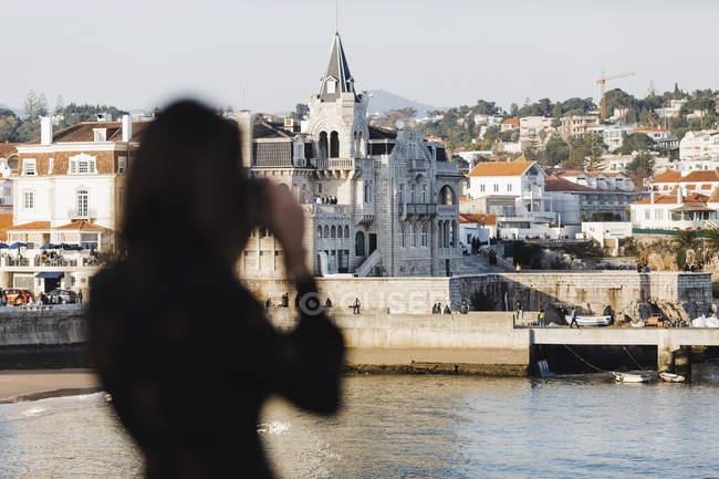 Silhouette female tourist photographing architecture, Cascais, Lisbon, Portugal — Stock Photo