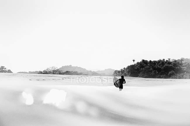 Surfer carrying surfboard into sunny ocean, San Pancho, Nayarit, Mexico — Stock Photo