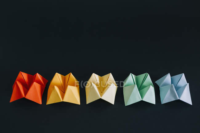 Rainbow multicolored origami fortune tellers on black background — Stock Photo
